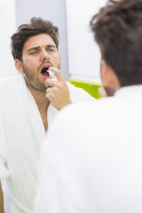 Reflection of man spraying medicine in mouth
