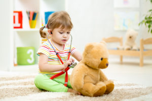 kid girl playing doctor with plush toy at home
