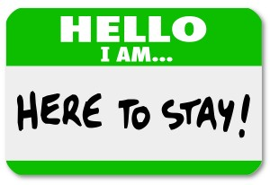 A namtag sticker with the words Hello I Am Here to Stay to symbo