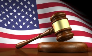 USA law and justice of The United States of America concept with a 3d render of a gavel on a wooden desktop and the flag of US on background.