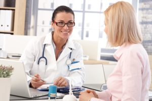 Happy female brunette doctor at medical office with patient, wri