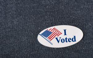 "Closeup of an American ""I voted"" sticker placed on a navy shirt."
