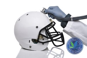 A football helmet and doctors hand holding a stethoscope on the