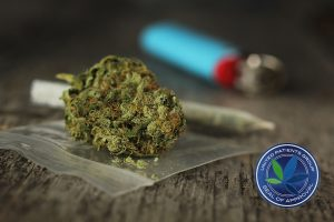 Closeup of marijuana joint and buds and blue lighter on a wooden