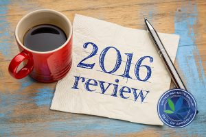 2016 review text on a napkin with coffee against grunge wood des