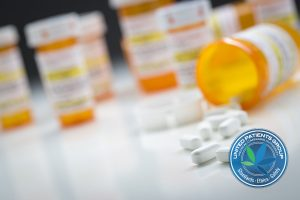 Variety of Medicine Bottles Behind Pills Spilling From Fallen Bo