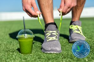 Green smoothie fitness man lacing running shoes, Athlete runner